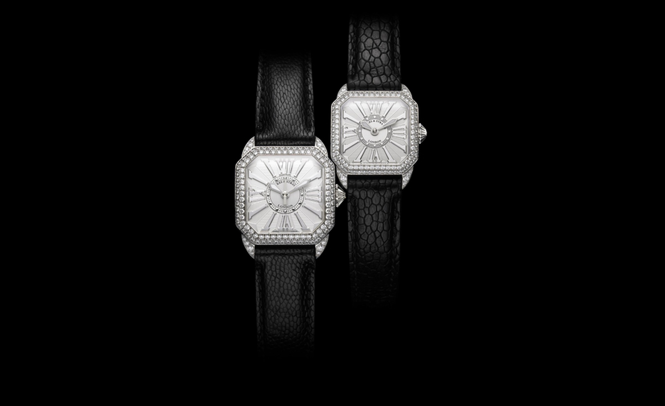 Backes & Strauss, pair of Berkeley watches in white gold. The white dial with white gold Roman numerals has 125  diamonds (2.39 carats). Price: £20,255. The second watch (behind) has 129 diamonds (1.77 carats). Price: £16,130