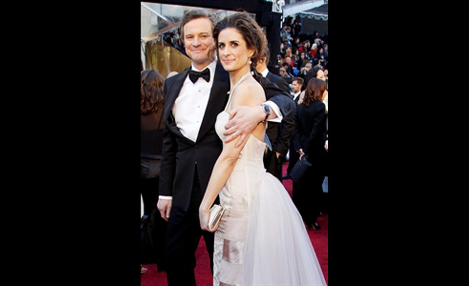Colin Firth with a Chopard on his wrist and his wife Livia Giuggioli tucked under his arm at the Oscars 2011