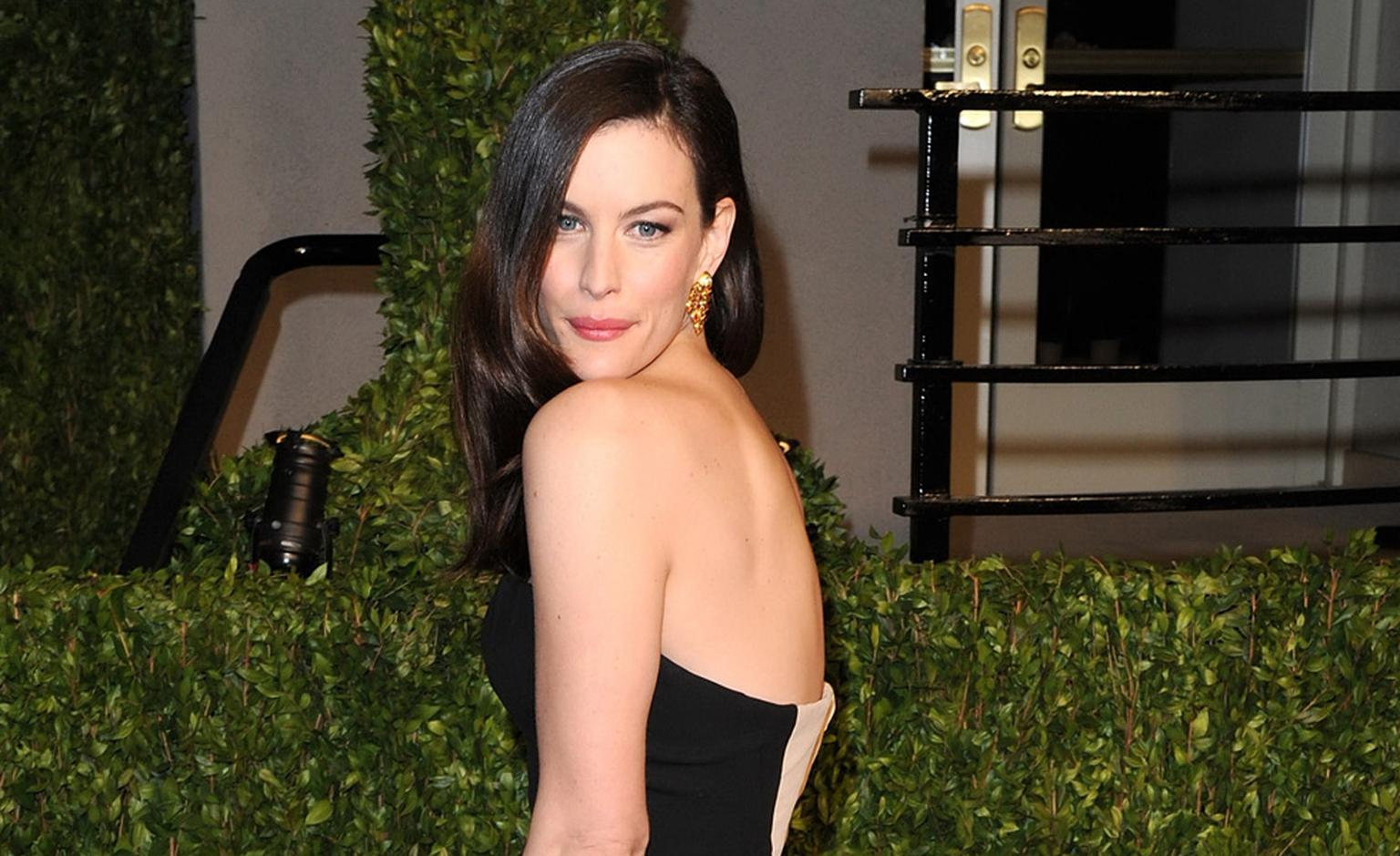 Liv Tyler wears Givenchy with Van Cleef & Arpels. The earrings 'fringe style' from 1969 with citrines and diamonds along with a yellow gold 1944 Ludo Hexagone  diamond ring and contemporary Perlée rose gold cuffs. Photo by Craig Barritt Getty Images