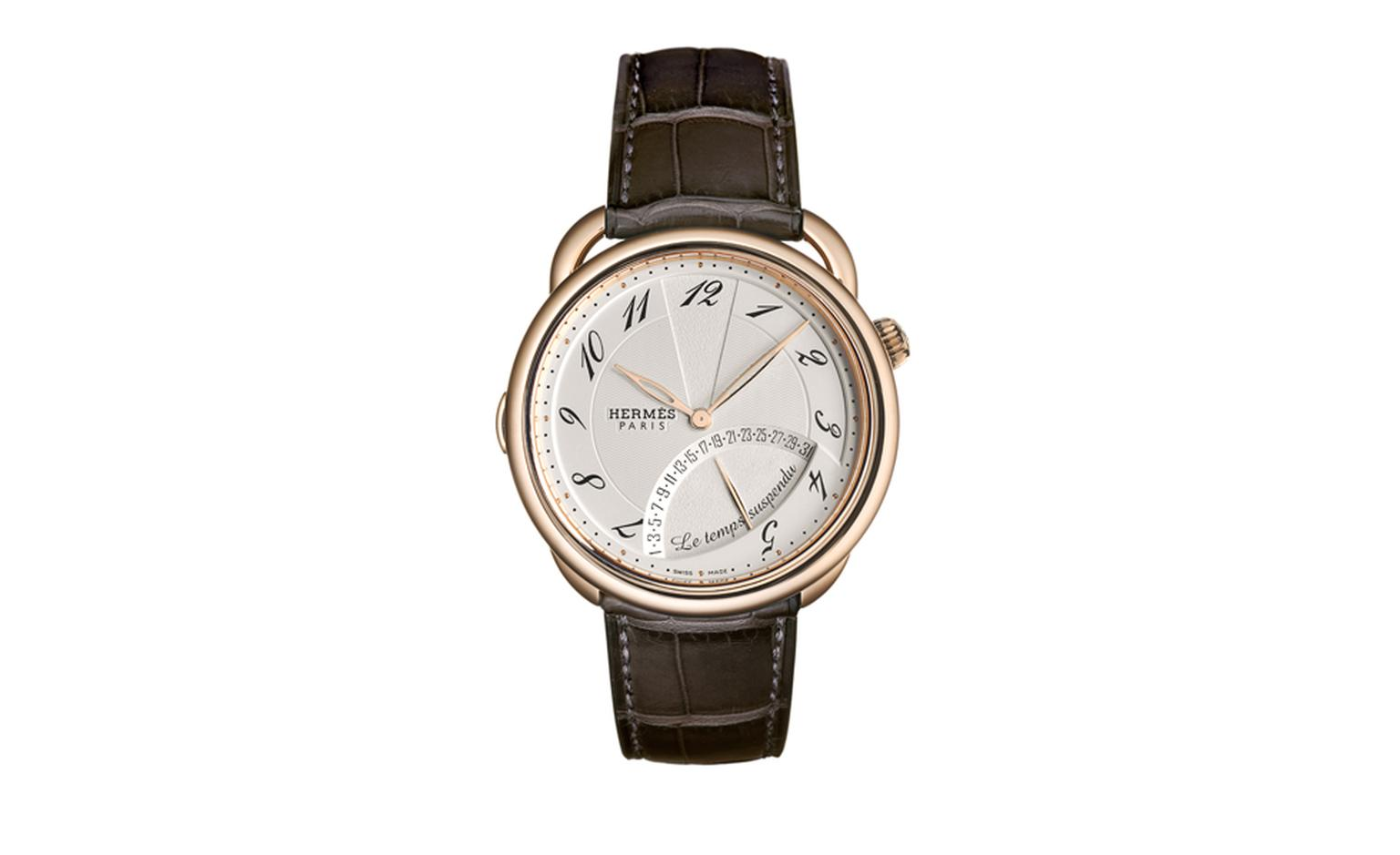 HERMES, Temps Suspendu is mechanical watch in rose gold with a brand new complication. Push the crown to suspend time at which point the two hands will sit at 12  o'clock until the crown is pushed again to resume timekeeping function.