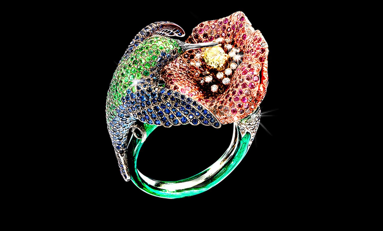 George Pragnell hummingbird ring is adorned with sapphires, green tsavorites and aquamarines and the flower is made up of rubies, pink sapphires and diamonds and at the centre is a fancy intense yellow diamond. Not for sale