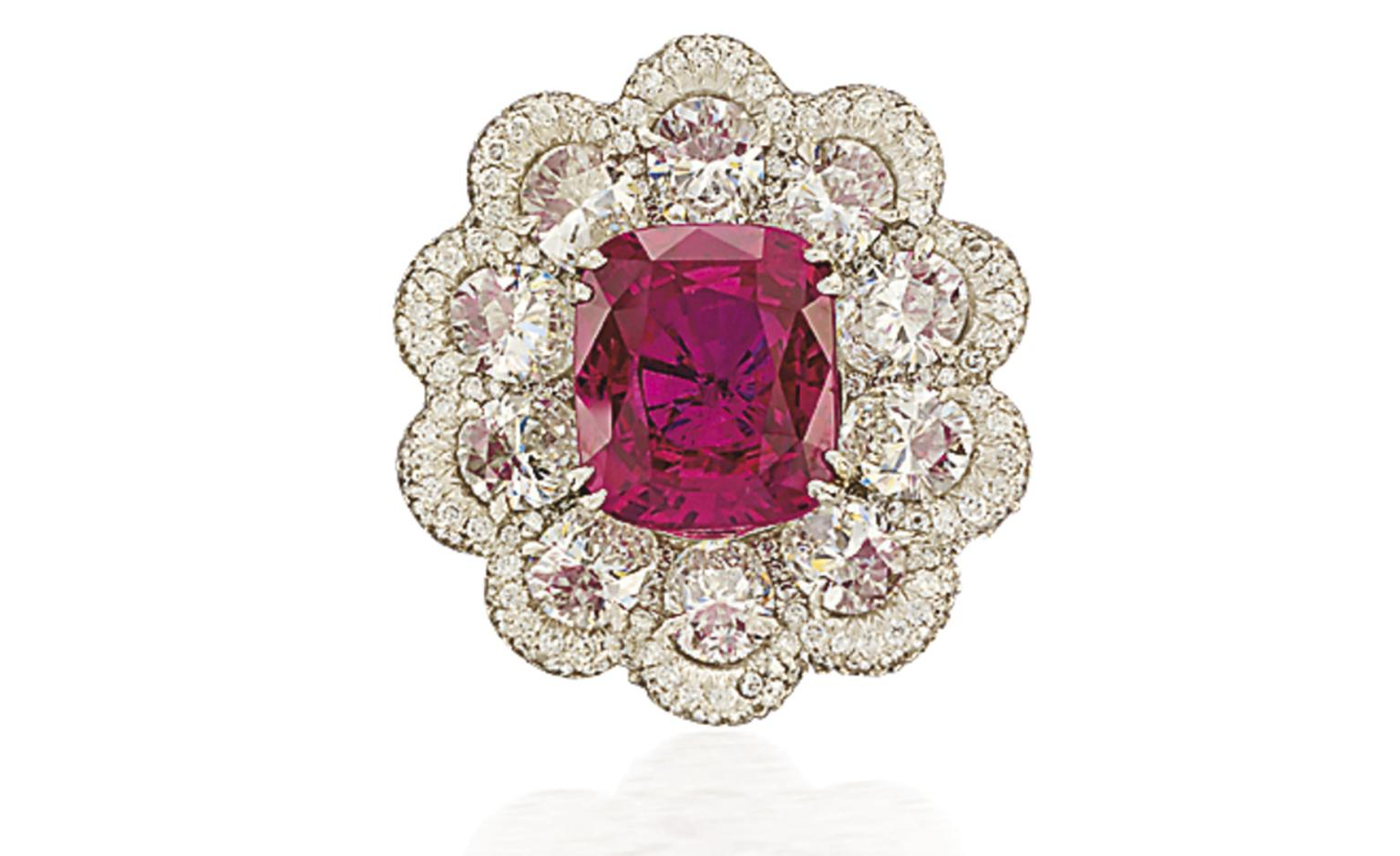 Lot 72. A fine ruby and diamond ring. Designed as a cluster centring upon a cushion-shaped ruby weighing 7.01 carats surrounded by oval-shaped diamonds weighing a total of 4.18 carats to the pavé-set diamond scalloped border and similarly-set di...