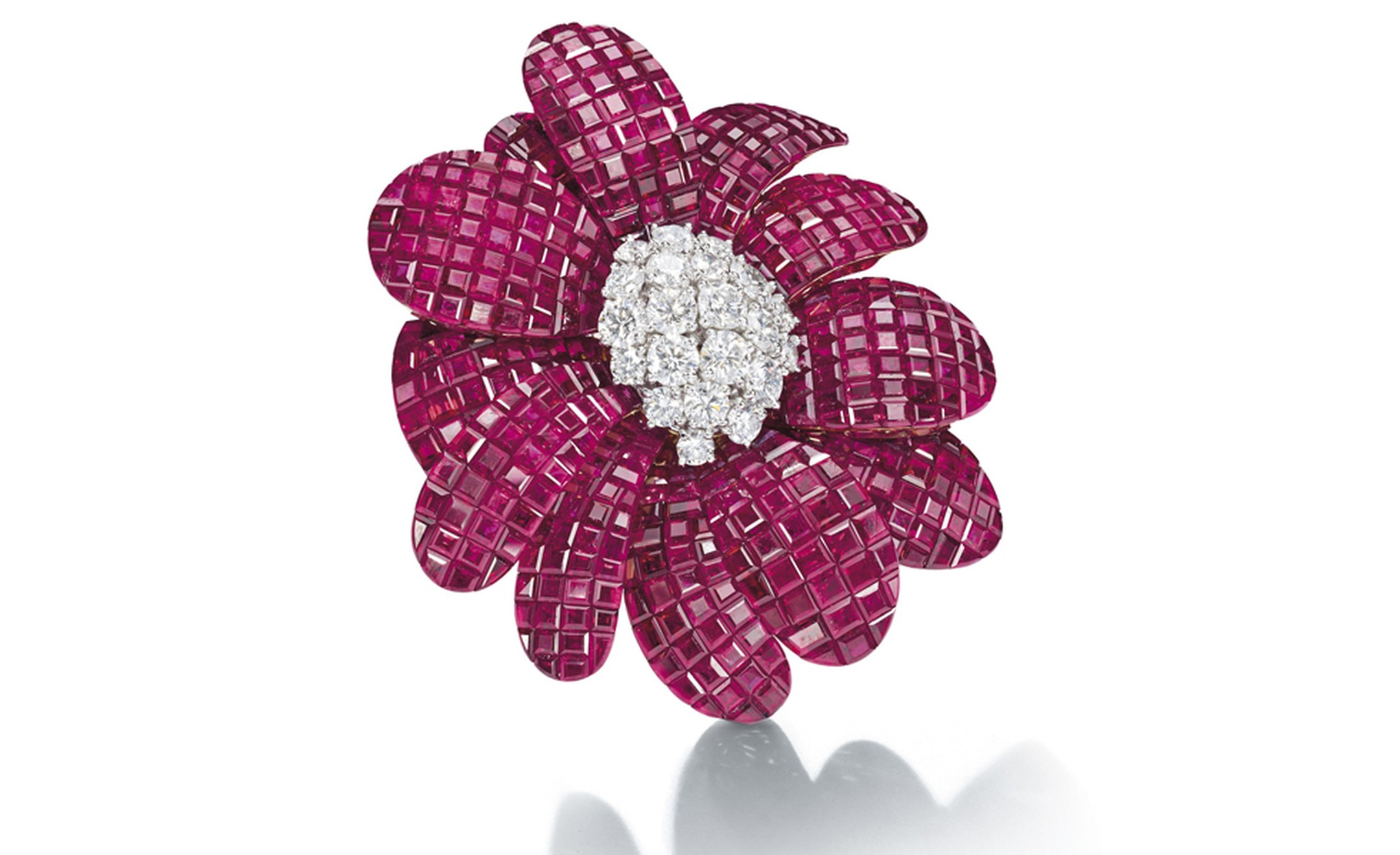 Lot 165. A ruby and diamond 'Cadix' Brooch, br Van Cleef & Arpels.Designed as a flowerhead, the mystery-set ruby petals centering on brilliant-cut diamond pistil mounted en tremblant, mounted in platinum and gold.  Estimate CHF 200,000 - CHF 300,000