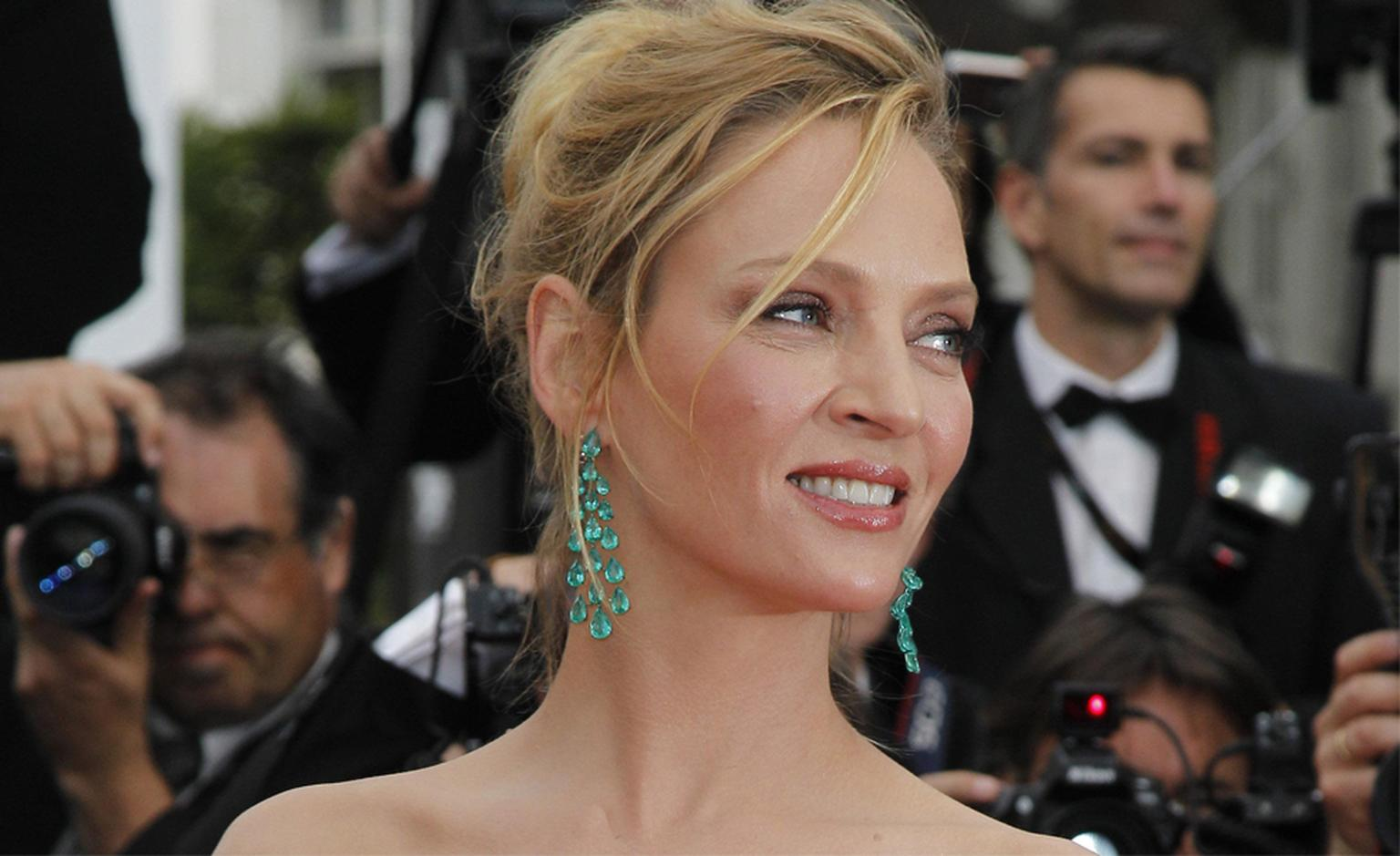 Uma Thurman in Chopard emerald chandelier earrings and bracelet.