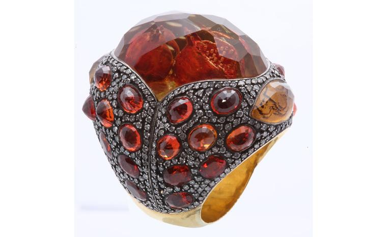 Sevan Biçakçi Pomegranate ring. The pomegranates are carved into the back of a precious stone that is mounted into the outsized ring set with diamonds.