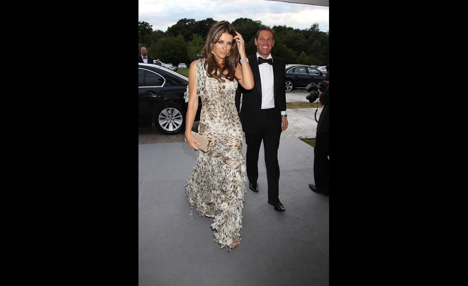Elizabeth Hurley makes a grand entrance in Chopard diamond earrings and bracelet and a Cavalli gown with beau Shane Warne a discreet few steps behind.