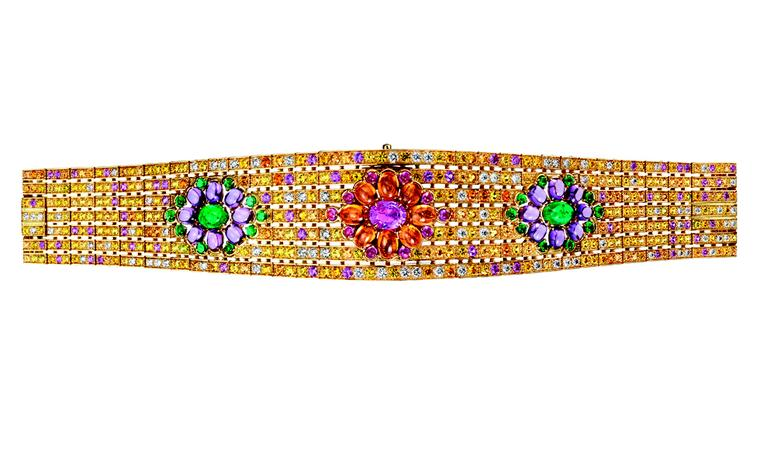 BOUCHERON. Isola Bella watch bracelet, set with a pink oval sapphire and pink and orange cabochon sapphirs, paved with yellow, pink and orange sapphires, emeralds and diamonds, on yellow gold. A watch is hidden under the central pattern. POA