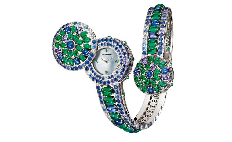 Boucheron Capriccioli watch bracelet paved with blue and purple round cabochon sapphires, oval cabochon emeralds,  blue and purple sapphires and diamonds, on white gold. A watch is hidden under the larger pattern of the bracelet. It opens by a s...