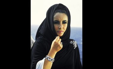 "Sardinia, 1968. American actress Elizabeth Taylor poses on the set of Joseph Losey's film ""Boom"" of 1968. She wears all Bulgari jewels, a ""Tremblant"" brooch in platinum with emeralds and diamonds and a ring in platinum with a step-cut octagonal ..."