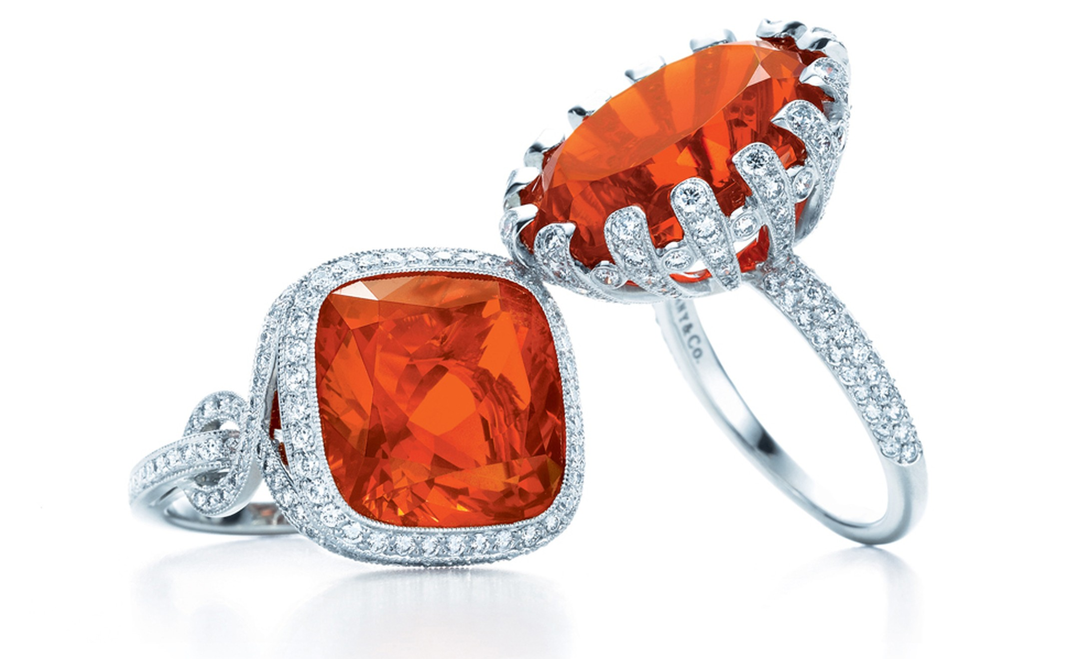 TIFFANY & CO. Cushion-cut fire opal in knot ring set in platinum oval fire opal in petals ring with diamonds set in platinums. POA