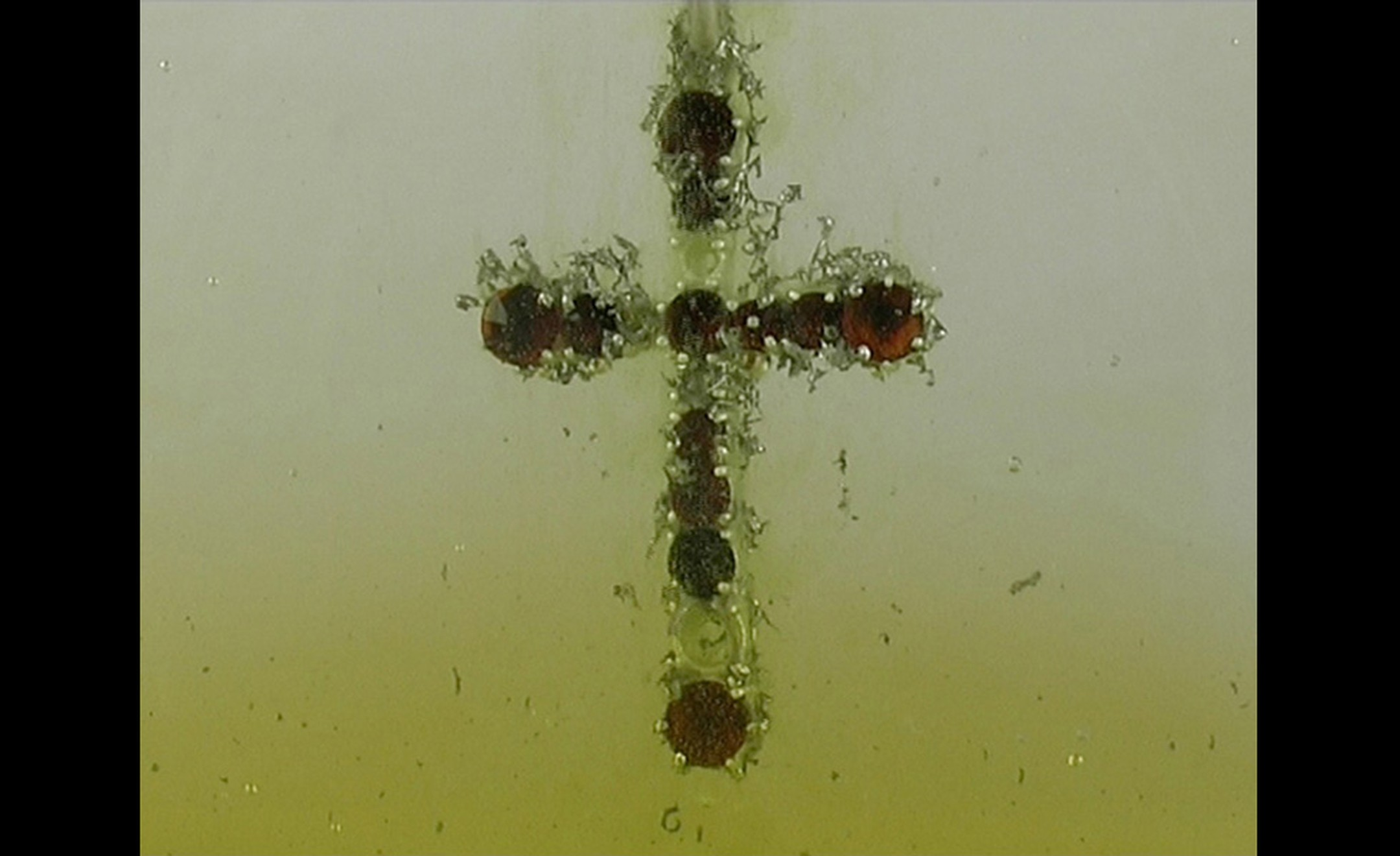 Gisbert Stach. Transformation cross pendant in silver with garnets in acid still image.