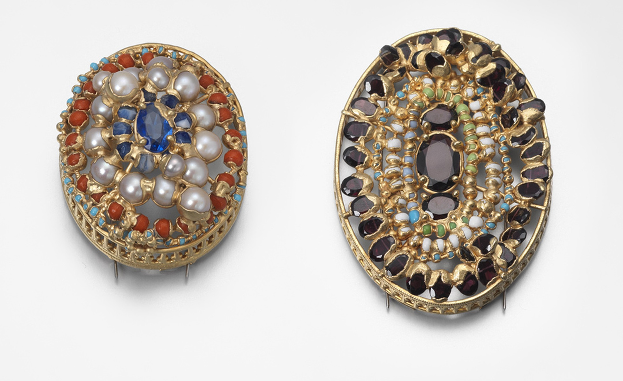 Brooches by Ruth Tomlinson. Yellow gold and silver brooch set with garnet, paste and antique glass measuring, price from £1950. Yellow gold and silver brooch set with pearls, West African glass, price from £1390